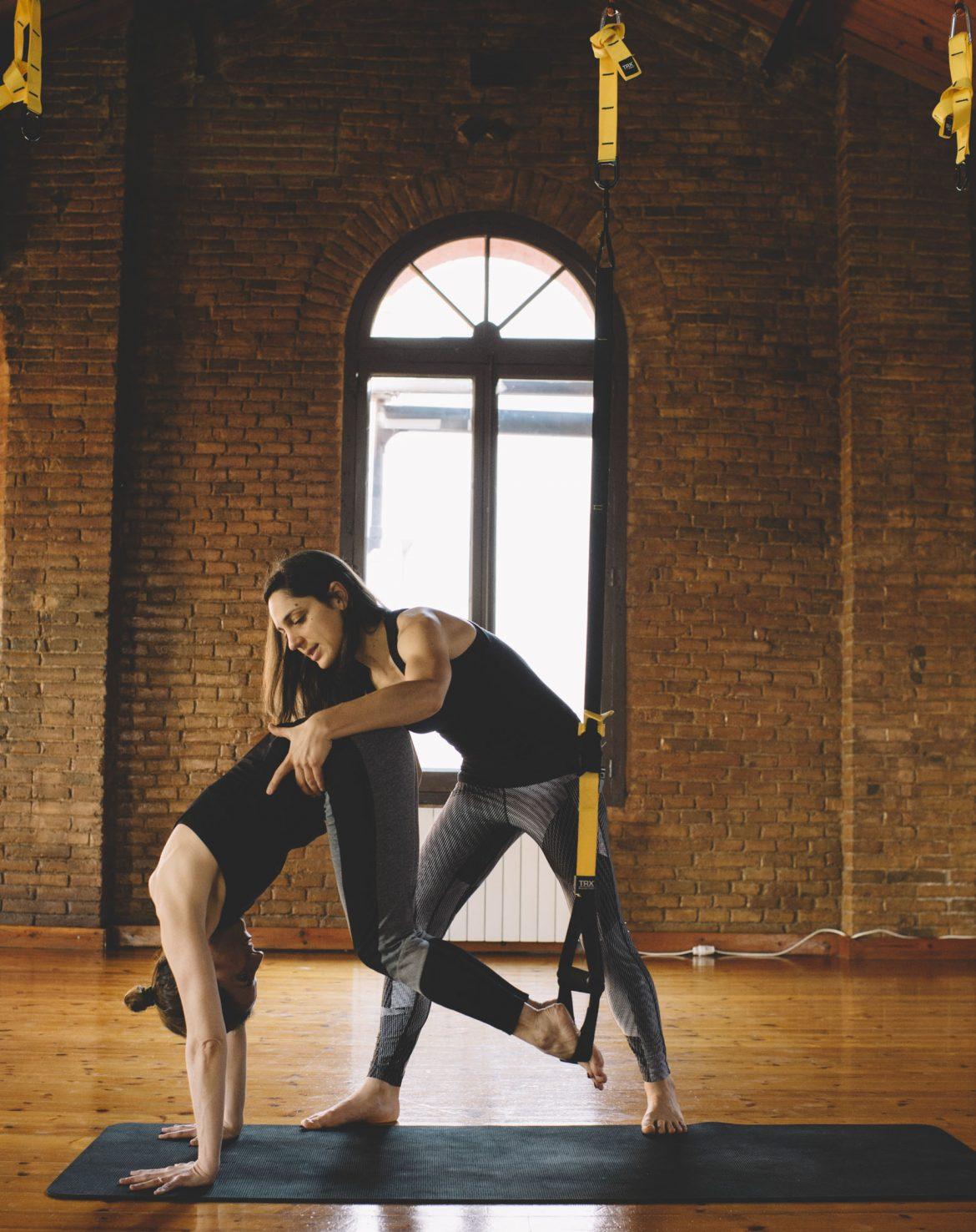 chica y profesora practicando yoga