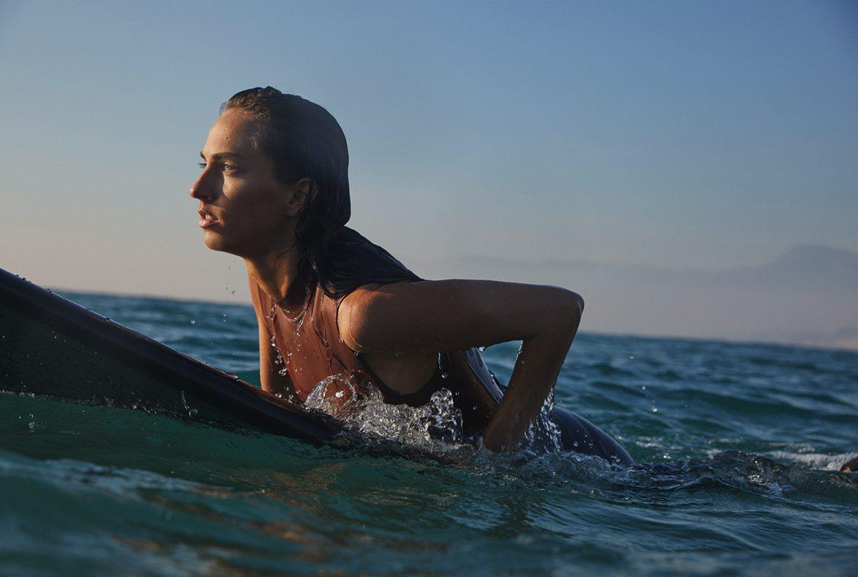 mujer sobre tabla de surf en el mar