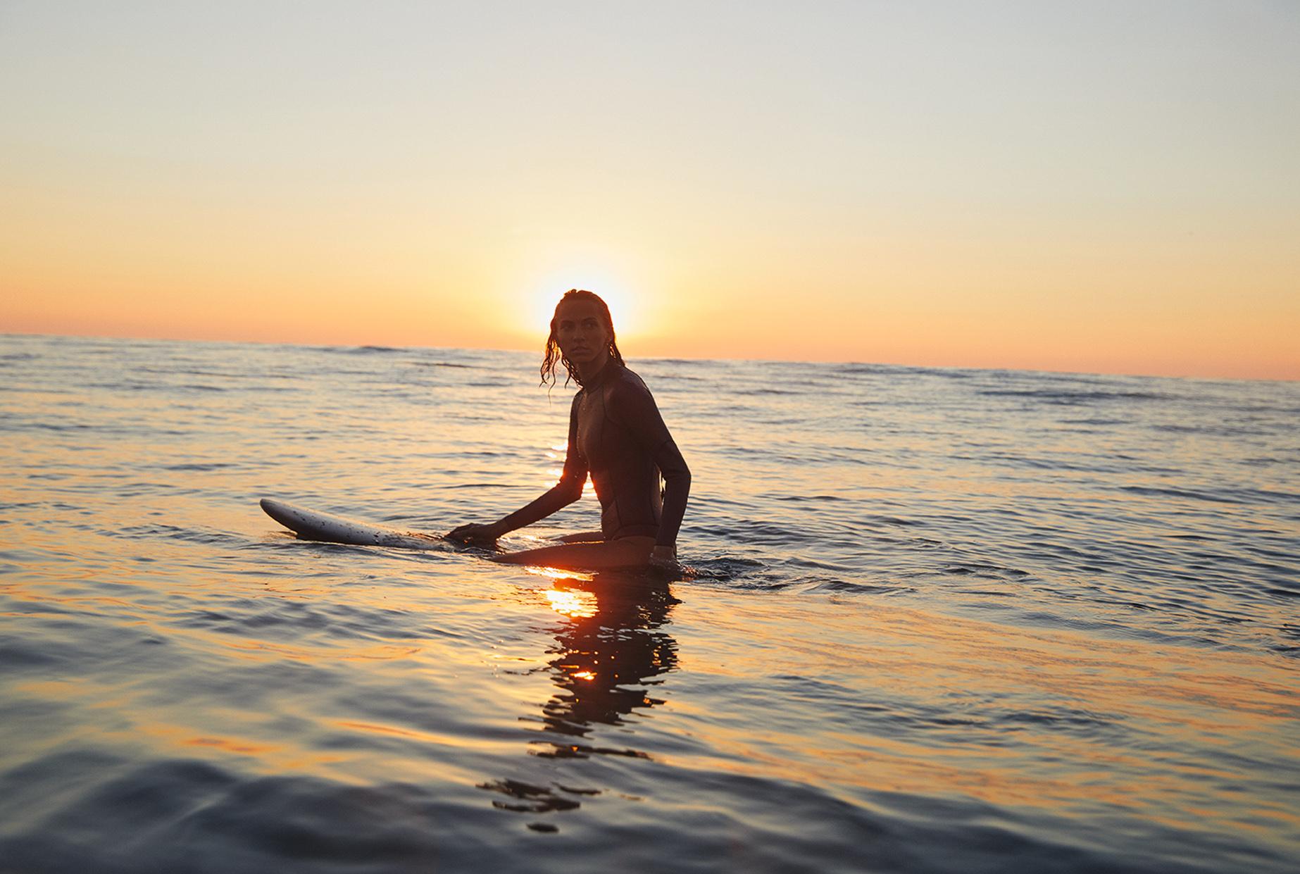 chica en el mar sobre tabla de surf